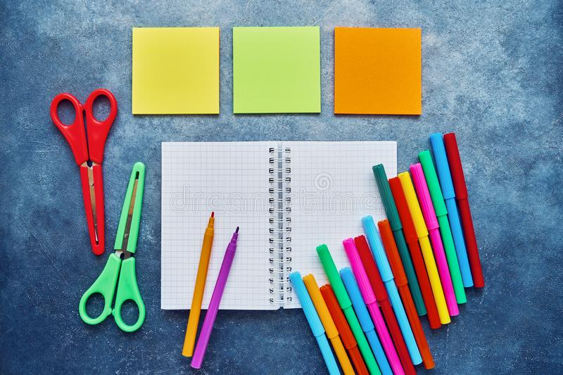 School subjects on a dark blue background. Back to school concept. Notepad, sticker pad, colored scissors and felt tip pens. Flat royalty free stock image