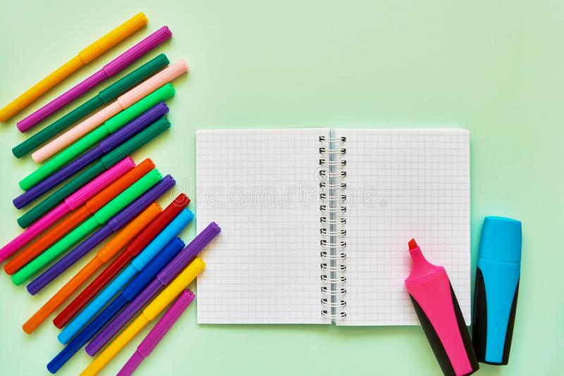 School subjects on green background. Felt tip pens and note pad on green backdrop. Back to school concept. Flat lay, copy space.  stock photos