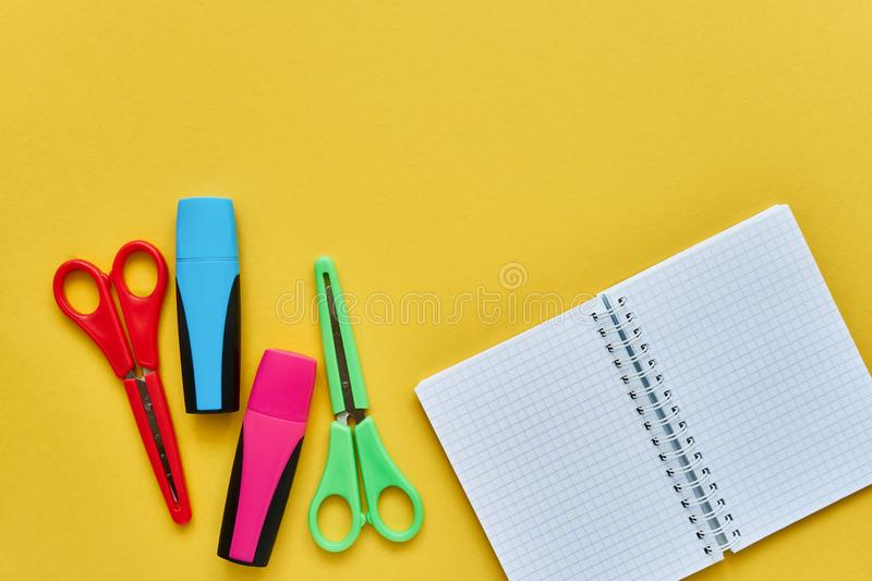School subjects on a yellow background. Notepad, colored scissors and felt tip pens. Back to school concept. Flat lay, copy space royalty free stock photos