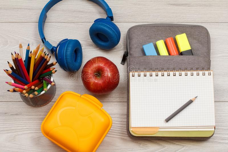 School supplies.. Apple, color pencils, lunch box, headphones and open exercise book on bag-pencil case on gray wooden boards royalty free stock photography
