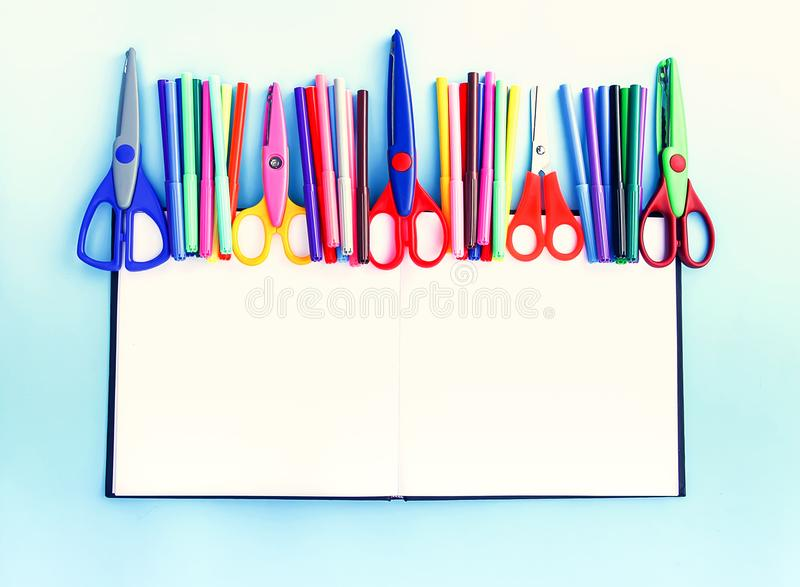 Back to School design elements. Colorful markers and scissors on opened empty notepad on light blue paper backgro royalty free stock images