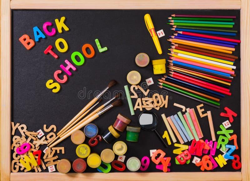 School supplies on blackboard background royalty free stock image