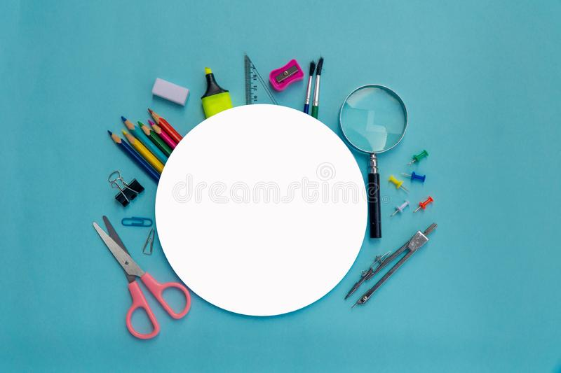 School supplies on blackboard background with round white paper ready for copy space stock photography