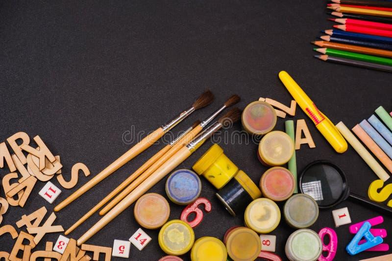 School supplies on blackboard black background royalty free stock photos