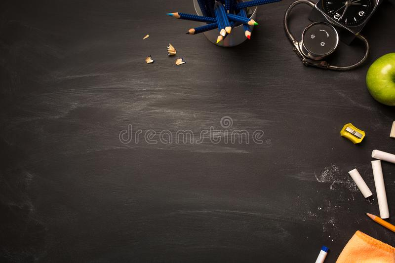 School supplies on blackboard. concept: back to school, school`s out, school holidays. School supplies, alarm, pencils, apple on black chalkboard top view, copy stock image