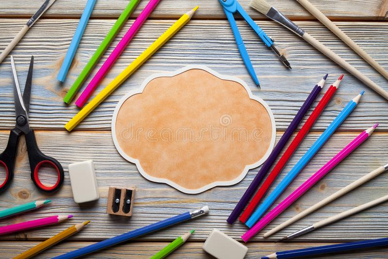 School supplies and blank label on wooden table. School supplies and blank label on wooden background royalty free stock images