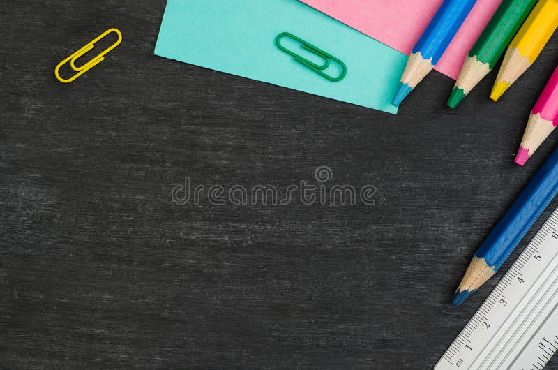 School supplies border on black chalkboard background. Top view photograph stock photography