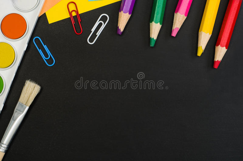 School supplies border on black chalkboard background. Top view photograph stock image