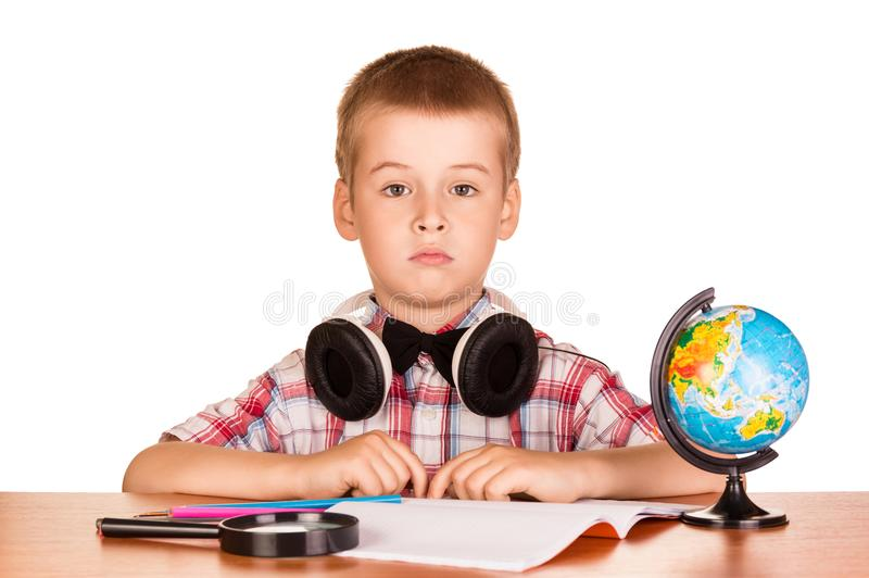 School supplies and boy with headphones engaged at the table, isolated on white stock photo