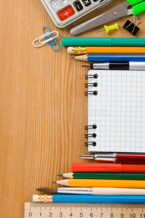 School supplies and checked notebook on wood royalty free stock photography