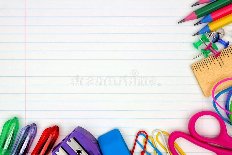 School supplies corner border on lined paper background stock photo