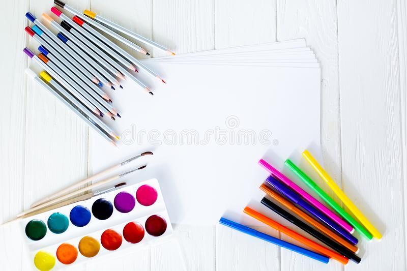 School supplies for drawing on the table: paper, pencils, paints, markers royalty free stock photo