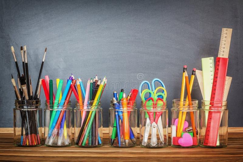 School supplies in jars stock photos
