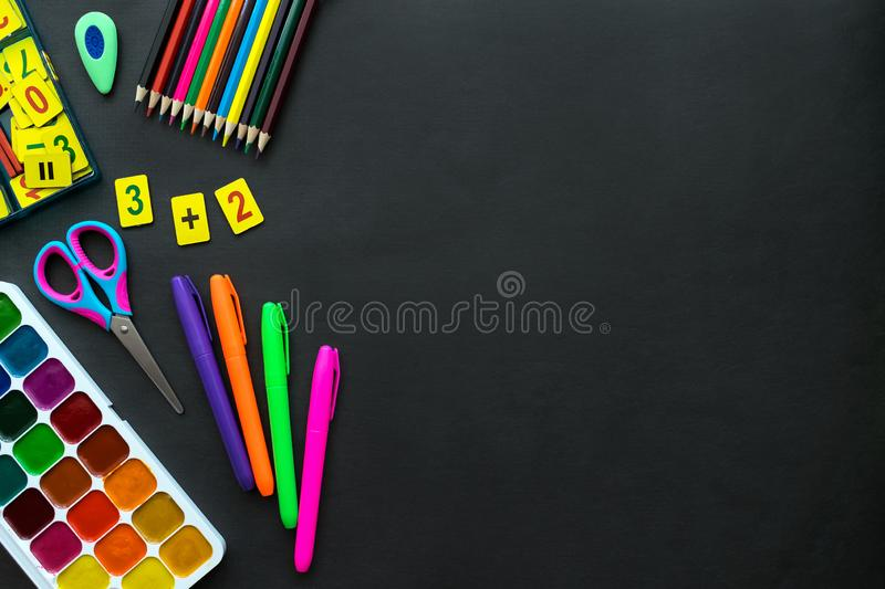 School supplies mockup on blackboard background with copyspace. Bright multicolored, pencils, pens, scissors, notepads, letters, figures, brushes, paints stock images