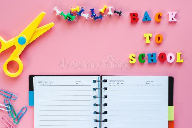 School supplies with wooden text BACK TO SCHOOL on pink background royalty free stock photos