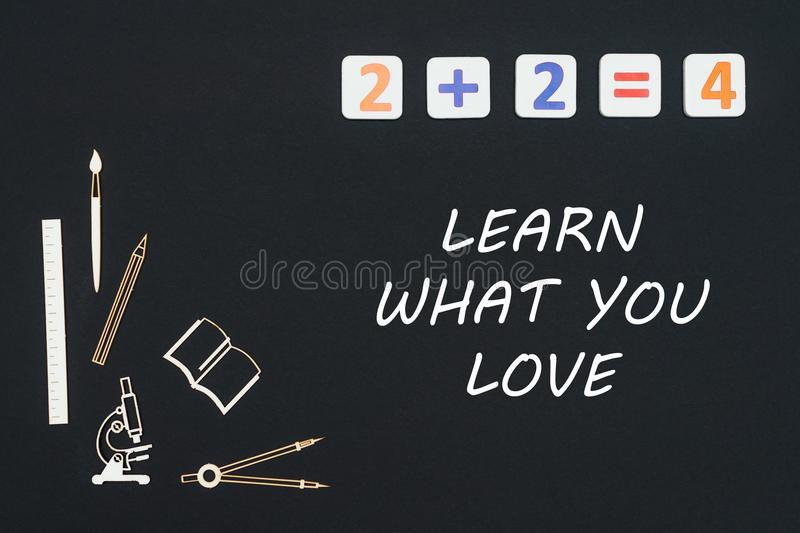 School supplies placed on black background with text learn what you love. Concept first class school, text learn what you love with wooden miniatures school royalty free illustration