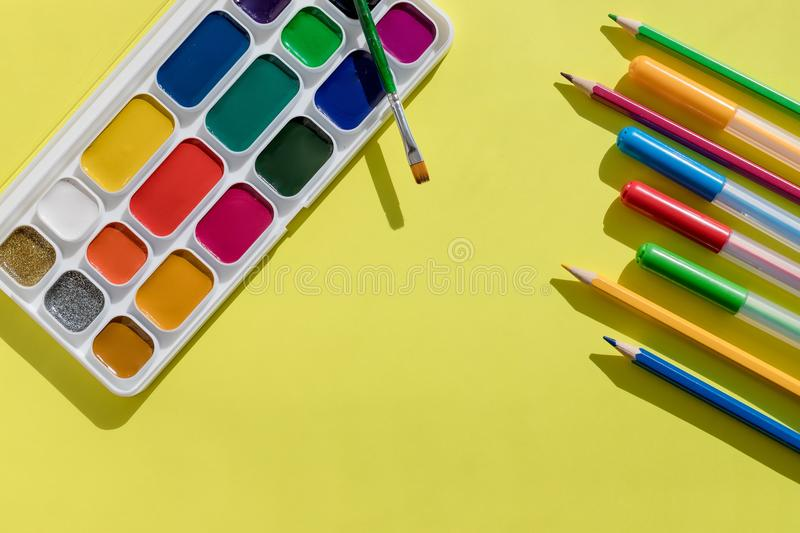 School supplies. A set of new watercolor paints, brushes and felt pens, markers, pencils lie on a light yellow royalty free stock photos