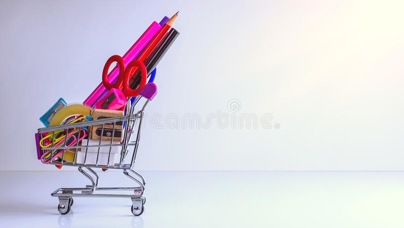 School supplies in shopping cart on white background stock photo