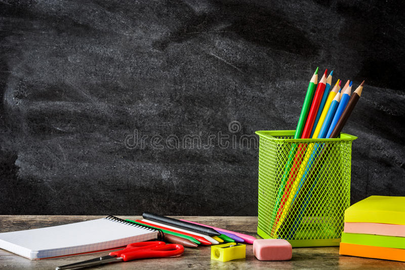 School supplies on wooden table and blackboard background. Back to school concept. stock photo