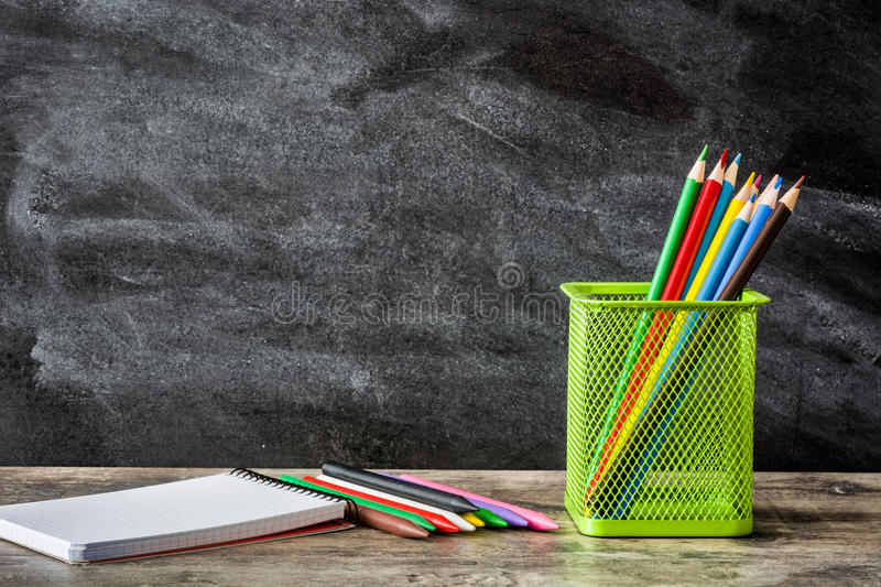 School supplies on wooden table and blackboard background. Back to school concept. royalty free stock photo