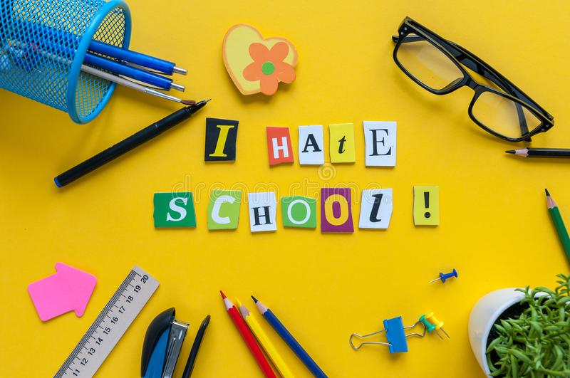 School supplies on yellow background with text I HATE SCHOOL.  stock photos
