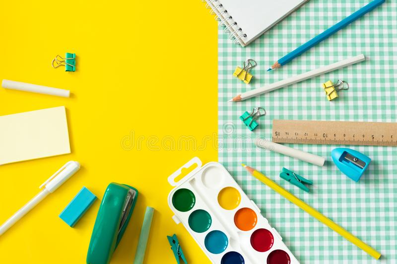 School supplies on yellow and blue checkered background stock photography