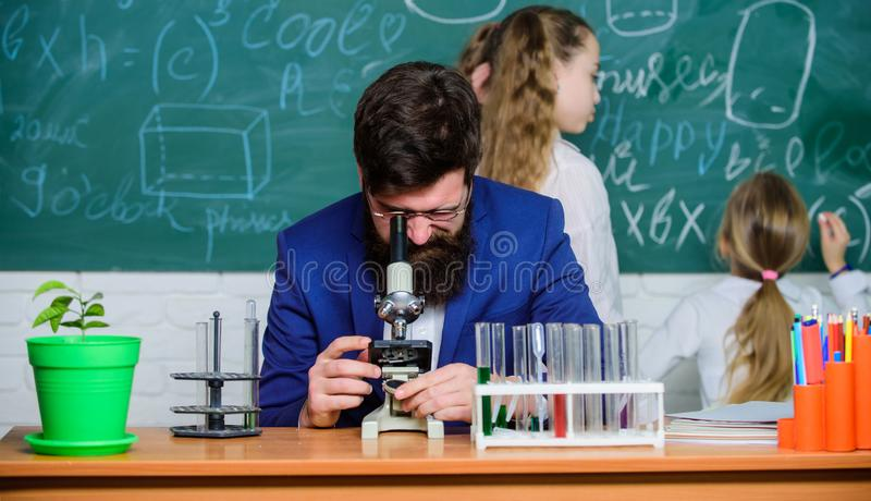 School teacher of biology. Man bearded teacher work with microscope and test tubes in biology classroom. Explaining. Biology to children. Biology plays role in stock photos