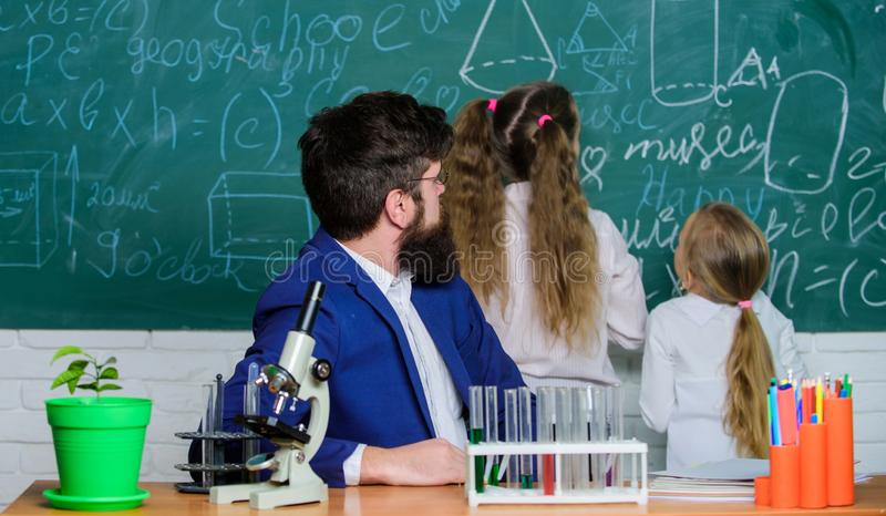 School teacher of biology. Man bearded teacher work with microscope and test tubes in biology classroom. Explaining. Biology to children. How to interest stock photos