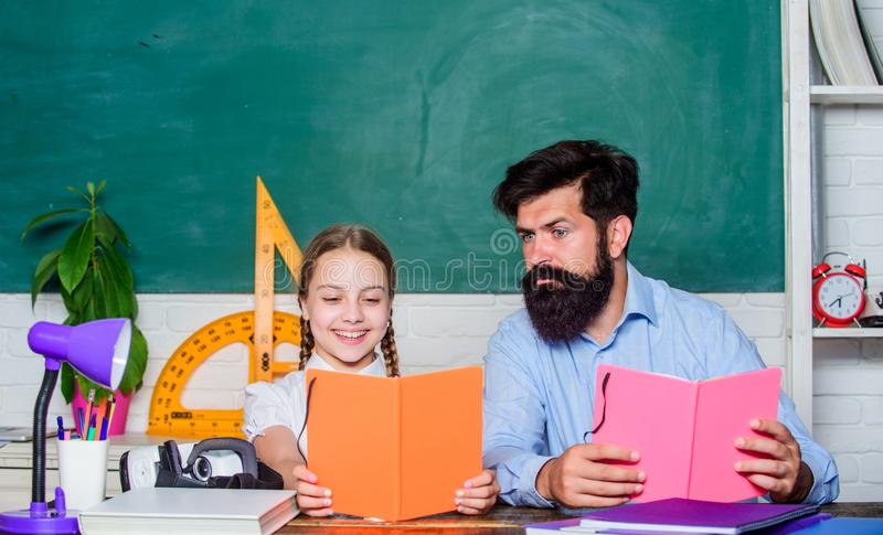 School teacher and schoolgirl. Task successfully done. Homeschooling with father. Help study. Discipline upbringing. Lesson is finished. Man bearded pedagogue stock images
