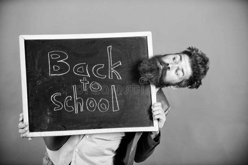 School and teacher wait for you. Teacher or bearded educator stands and holds blackboard with inscription back to school. Red background. Teacher informs back stock images