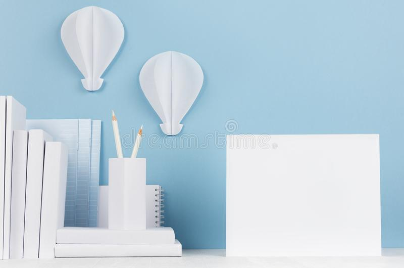 School template - white books, stationery, blank notebook and decorative ballons origami on white desk and soft blue background. royalty free stock photo