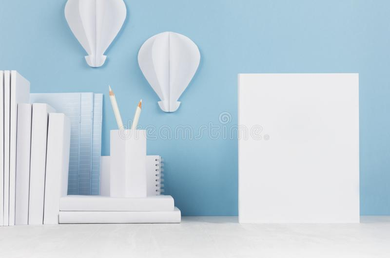 School template - white books, stationery, blank paper and decorative ballons origami on white desk and soft blue background. royalty free stock photography
