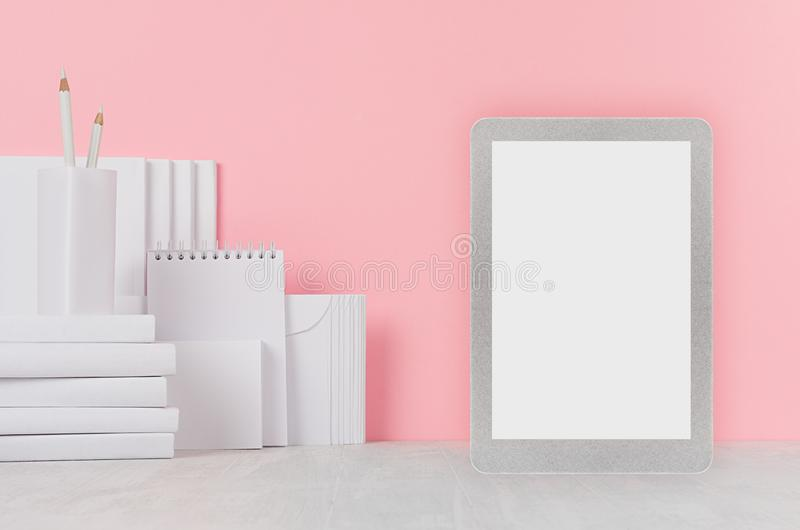 School template - white books, stationery, blank stickers and tablet computer on white desk and soft pink background. stock image