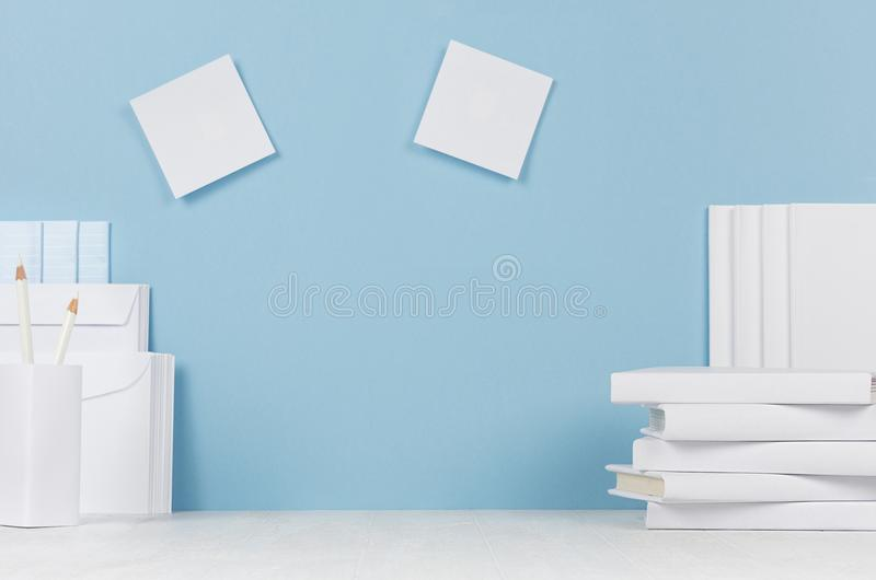 School template - white books, stationery, blank stickers on white desk and soft blue background. Back to school background with copy space stock photography