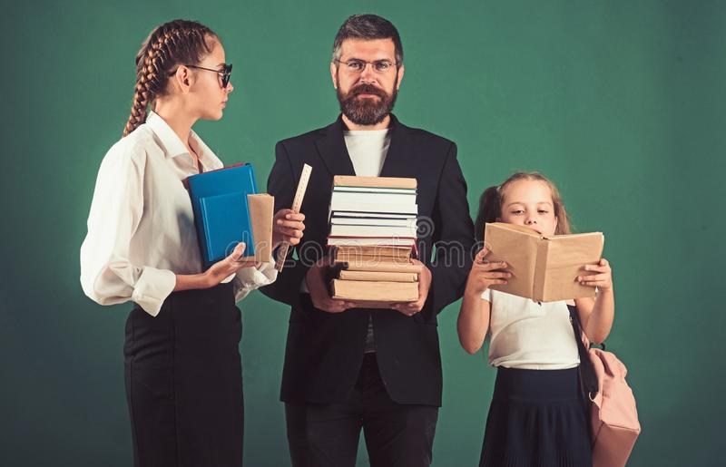 School time of sisters and father in library. Literature lesson and reading grammar book. Education in knowledge day. Teacher men and girls hold book pile at royalty free stock photos