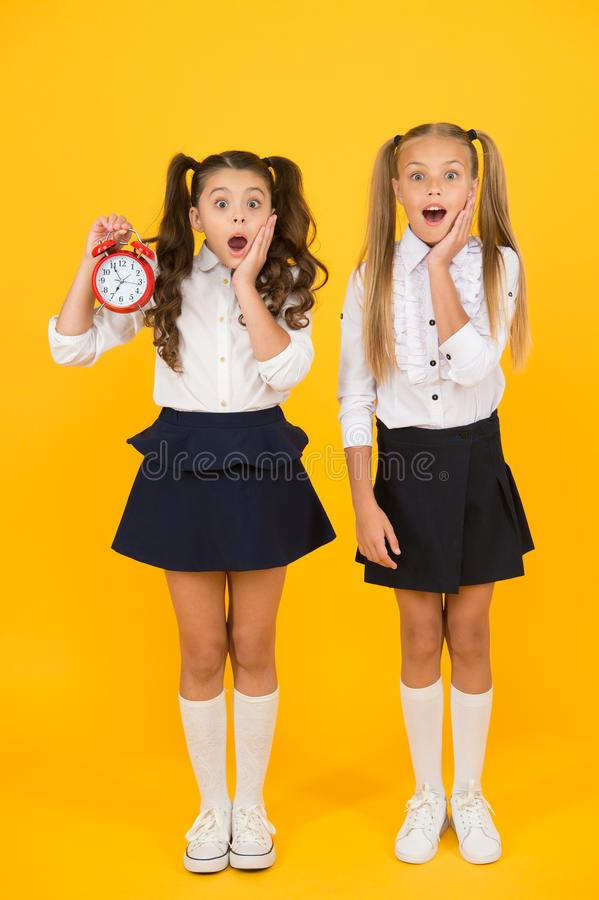 School time. Surprised shocked kids hold alarm clock counting time. Latecomer will be punished. It is time. School. Schedule. Schoolgirls and alarm clock stock image