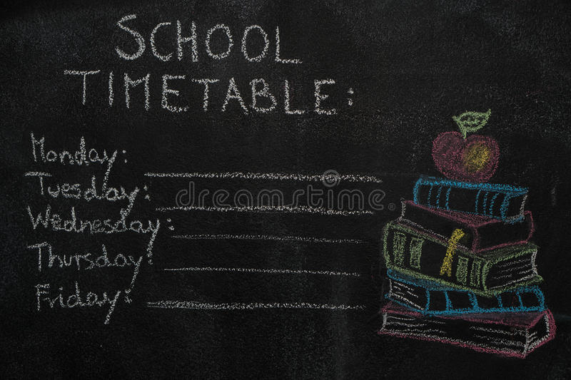 School timetable and stack of books with apple drawn on black chalkboard royalty free stock photo