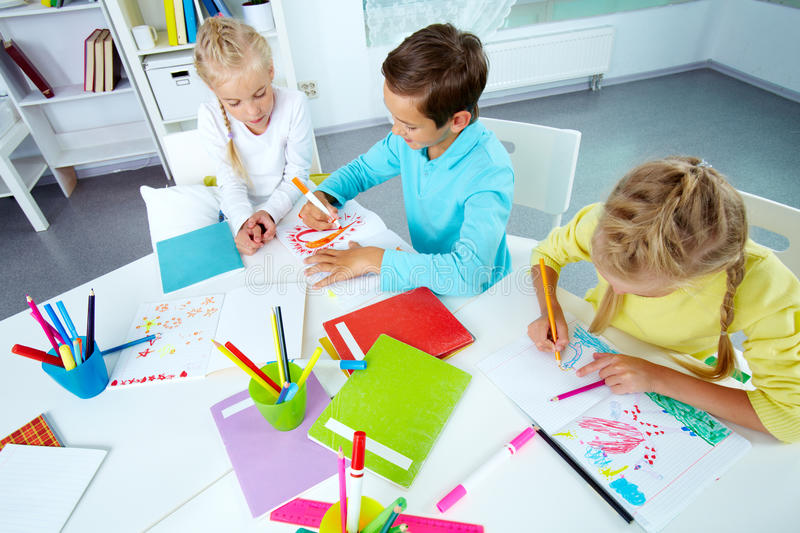 After school. Trio of friends enjoying drawing in an after-school club stock images