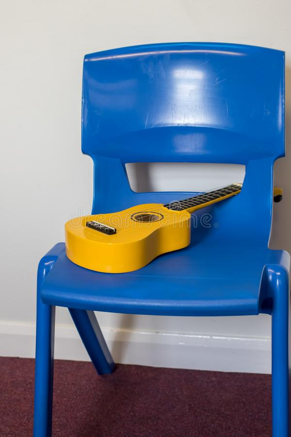 School ukulele lesson. Yellow uke left in music room. Musical instrument on blue plastic chair royalty free stock photography