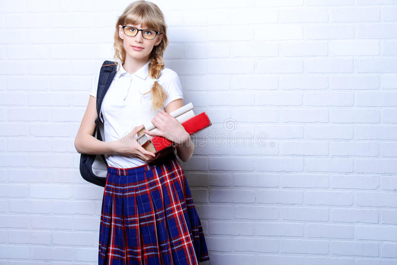 School uniform. Pretty teen girl wearing school uniform and school bag. Education. Studio shot stock image