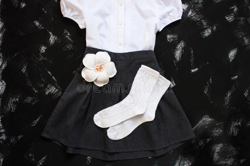 School uniform with white shirt, socks and dark denim skirt on a black background. Flatlay, top view, copy space stock photos