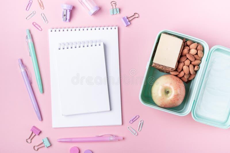 Schoolachtergrond met notitieboekjes en toebehoren van de pastelkleur de kleurrijke studie op roze achtergrondlunchdoos met appel stock fotografie