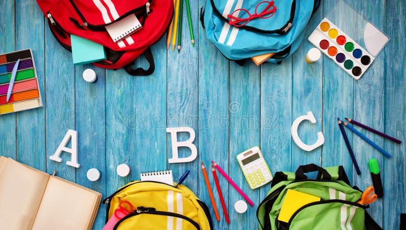 Schoolbags coloridos das crianças no assoalho de madeira fotos de stock royalty free