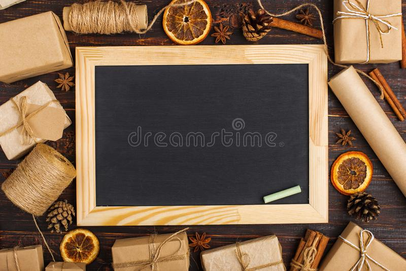 Schoolbord in het midden van giften van droge sinaasappel, kaneel, denneappels, anijsplant op een witte lijst Kerstmisstaaf, spar royalty-vrije stock afbeelding