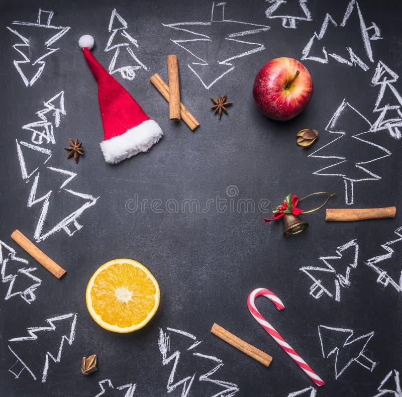 Schoolbord met geschilderde Kerstmisdecoratie, Kerstbomen, suikergoed, koppen en ingrediënten voor overwogen wijn, kader, ruimtef stock illustratie