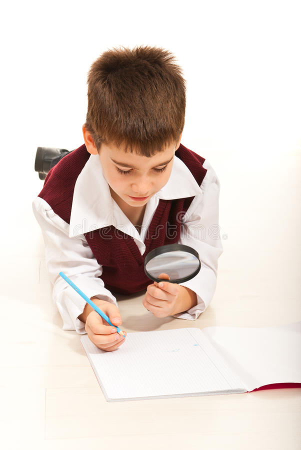 Schoolboy με το πιό magnifier σπίτι στοκ εικόνες με δικαίωμα ελεύθερης χρήσης