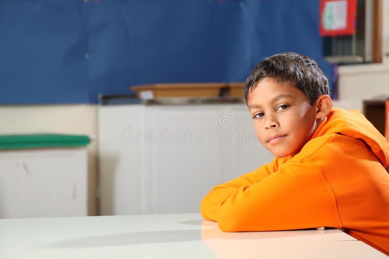 Schoolboy 10 arms folded deep in thought classroom stock photos