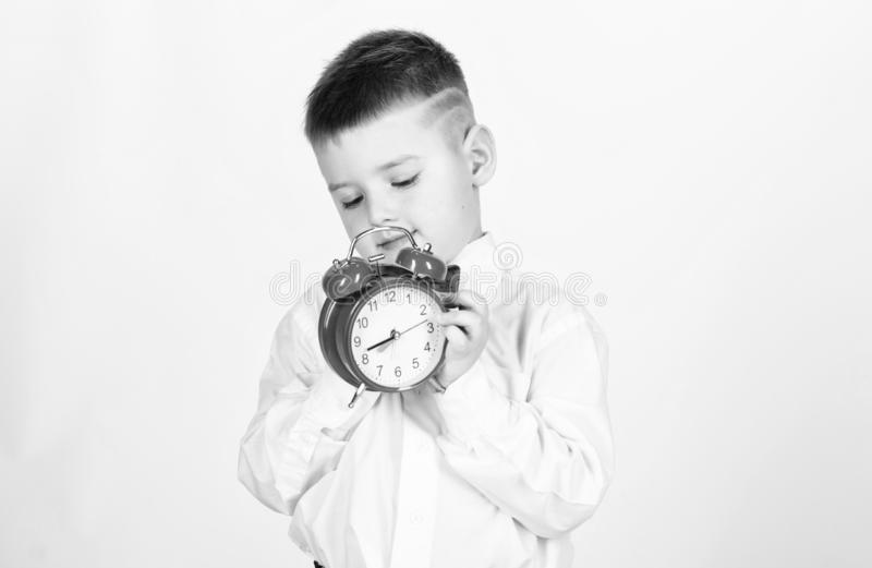 Schoolboy with alarm clock. Kid adorable boy white shirt red bow tie. Develop self discipline. Set up alarm clock. Child. Little boy hold red clock. It is time royalty free stock images
