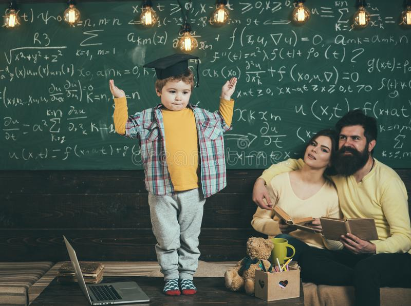 Schoolboy answer lesson at chalkboard. Little schoolboy in graduation cap. Schoolboy and family in classroom. Man and stock photography