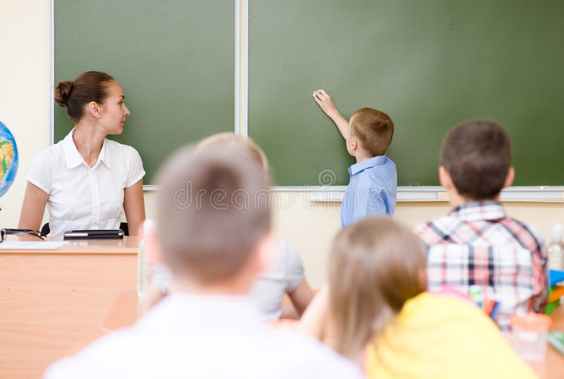 Schoolboy answers questions of teachers near a school board.  royalty free stock images